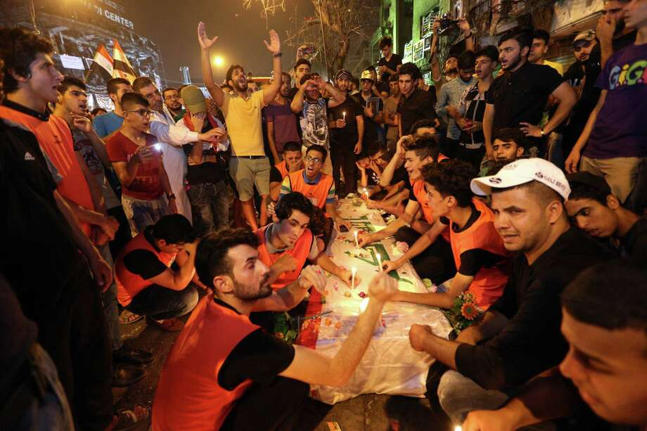 Mourners grieve as they light candles over the Iraqi flag-draped coffins of bomb victims at the scene of a massive car bomb attack in Karada, a busy shopping district where people were shopping for the upcoming Eid al-Fitr holiday, in the center of Baghdad, Iraq, Monday, July 4, 2016. (AP Photo/Hadi Mizban) ORG XMIT: ZHM122 Photo: Hadi Mizban / Copyright 2016 The Associated Press. All rights reserved. This m