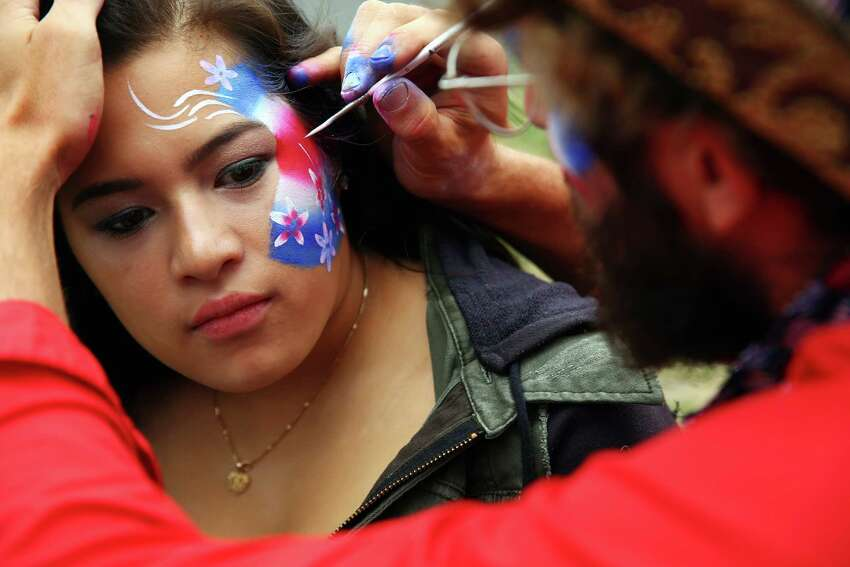 Ty Campbell paints a patriotic design on Pearl Nguyen's face during Fourth of July celebrations at Gas Works Park, Monday, July 4, 2016.