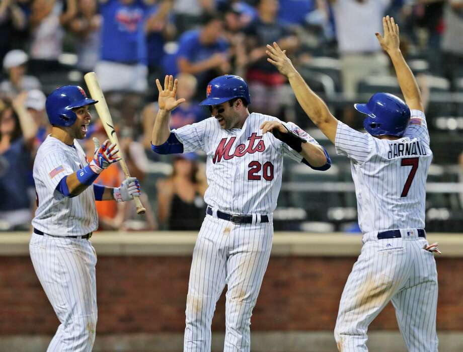 New York Mets' Neil Walker, center, and Travis d'Arnaud, right, celebrate scoring on a double hit by Yoenis Cespedes with teammate James Loney, left, during the eighth inning of the baseball game against the Miami Marlins at Citi Field, Monday, July 4, 2016 in New York. The Mets defeated the Marlins 8-6. (AP Photo/Seth Wenig) ORG XMIT: NYSW118 Photo: Seth Wenig / Copyright 2016 The Associated Press. All rights reserved. This m