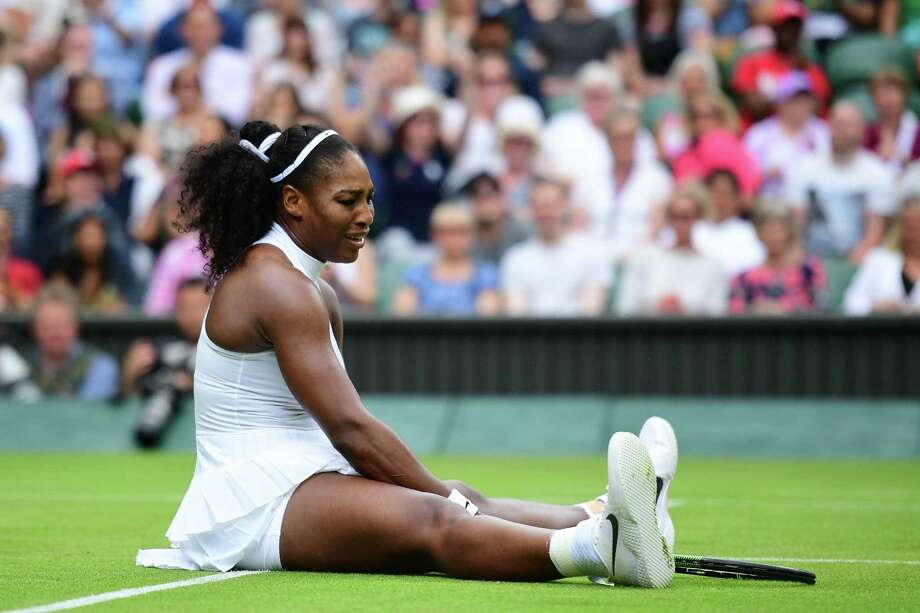 TOPSHOT - US player Serena Williams sits on the court after slipping while playing Russia's Svetlana Kuznetsova during their women's singles fourth round match on the eighth day of the 2016 Wimbledon Championships at The All England Lawn Tennis Club in Wimbledon, southwest London, on July 4, 2016. / AFP PHOTO / LEON NEAL / RESTRICTED TO EDITORIAL USELEON NEAL/AFP/Getty Images Photo: LEON NEAL / AFP or licensors