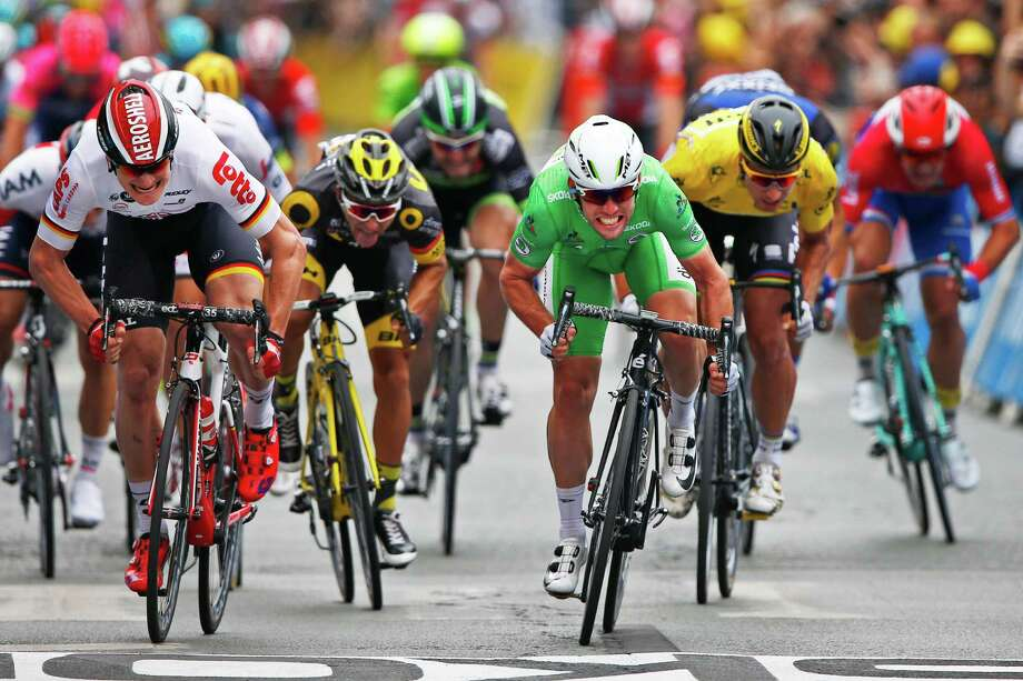Britain's Mark Cavendish, wearing the overall leader's yellow jersey, crosses the finish line ahead Germany's Andre Greipel, left, and Peter Sagan of Slovakia, wearing the overall leader's yellow jersey, to win the third stage of the Tour de France cycling race over 223.5 kilometers (138.6 miles) with start in Granville and finish in Angers, France, Monday, July 4, 2016. (AP Photo/Peter Dejong) ORG XMIT: PDJ125 Photo: Peter Dejong / AP