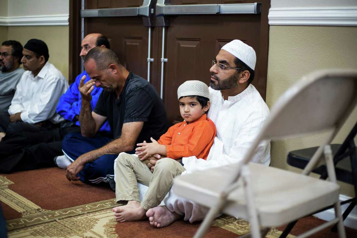 A young boy sits in his father's lap as fellow members of the congregation listen to a sermon on the problems of slander during a Ramadan service at the Muslim Children Education and Community Center in San Antonio, on Friday, June 24, 2016.