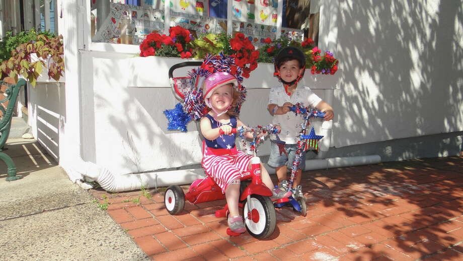 Lena Sizensky, 3, of Southport, and Jaxson Snyder, 3, of Fairfield, wait by Switzer's Pharmacy in Southport for Pequot Library's July 4th Bike Parade to begin Monday morning. Photo: Mike Lauterborn / For Hearst Connecticut Media / Fairfield Citizen