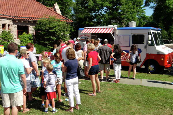 Families line up for lunch from the Super Duper Weenie truck at Pequot Library during July 4th festivities Monday morning.