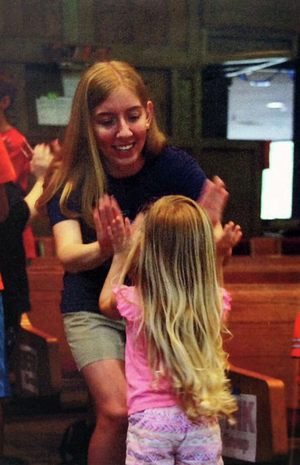 Sam Houston State University sophomore Julie Mulkey gives Hope Jyrkama a high-five at Camp Hope.