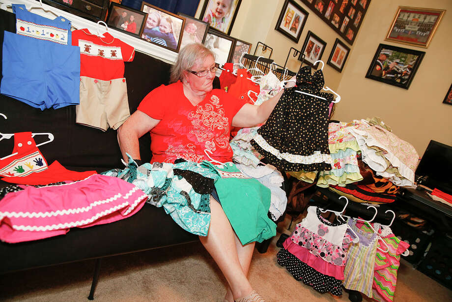 Retired Katy Independent School District elementary teacher Donna Summers shows off the baby dresses, jumpers, and other clothing that she sells from her home. Photo: Diana L. Porter, Freelance / © Diana L. Porter
