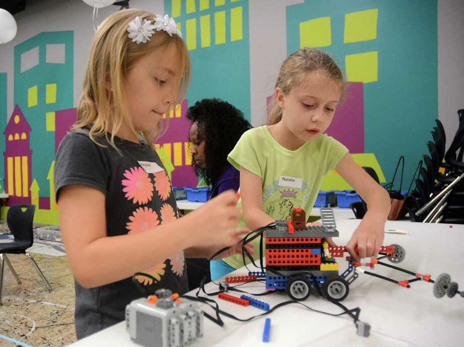 Haylee Passmore, left, and Natalie Hilbrich prepare the Lego robot they built for a robotics soccer game during The Woodlands Children's  Museum's robotics workshop. The museum is hosting an 11-week summer workshop series for children. Photo: Z-David Hopper