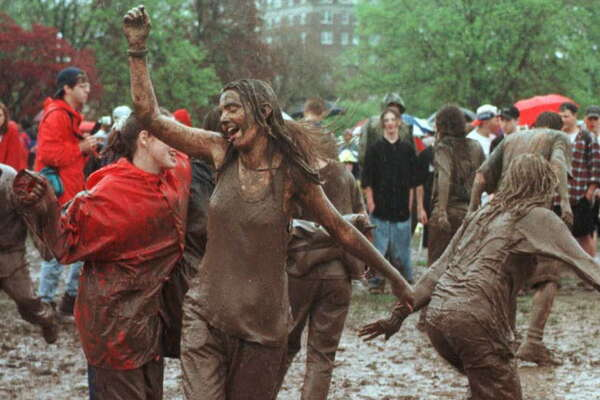 Times Union Photo by Luanne M. Ferris:   Tulip Festival turns to mud festival as people waiting for tonight's Spin doctors concert dance to radio music in Washington Park Saturday may11,1996.      for Jakes story
