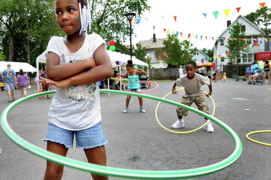 Cheyuani Jones, 7, of Atlanta, left, who's in town visiting family, hula hoops during the Delaware Library's Summer Fest on Saturday, July 7, 2012, in Albany, N.Y. Joining her are her cousin Nianna Tatro, 6. center, and Mickel Frost, 6. (Cindy Schultz / Times Union) Photo: Cindy Schultz / 00018381A