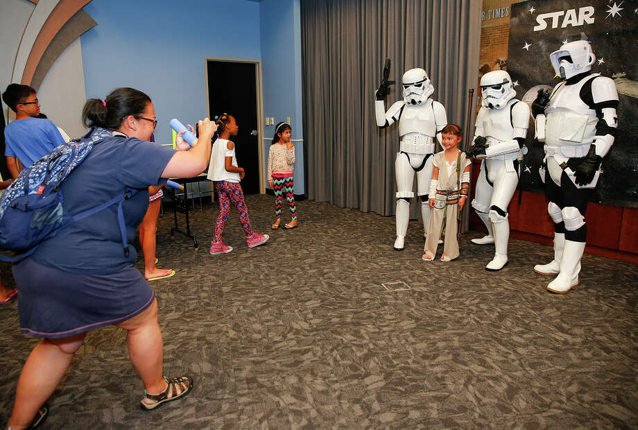 Louise McEvoy takes a picture of her daughter Charlee, 6, in her Star Wars costume with imperial stormtroopers at a Star Wars craft event at the Sugar Land Branch Library. Photo: Diana L. Porter, Freelance / © Diana L. Porter
