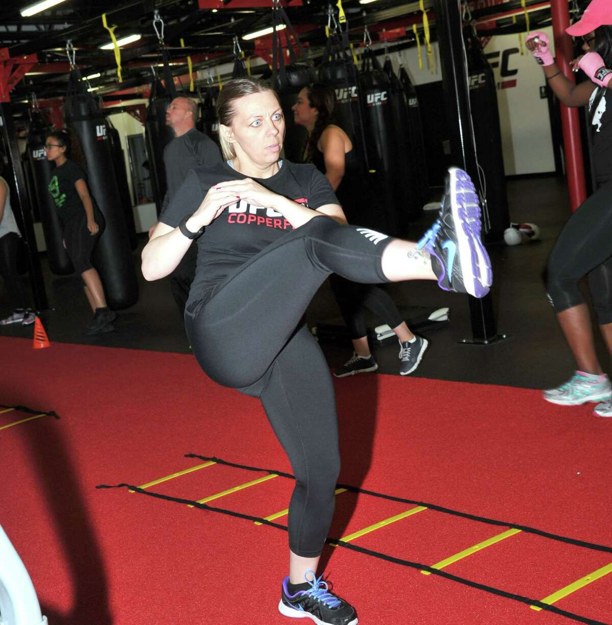 Kristyna Anaya practices her high kick as part of her workout at UFC Gym Copperfield. The gym, which bases workouts on training techniques used by mixed-martial arts fighters, opened more than a year ago.