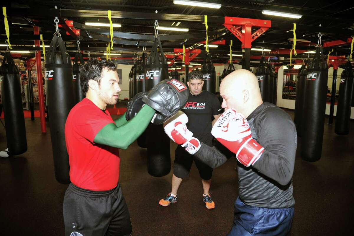 The UFC Gym in West Houston, operated by Steve and Ana Marie Hernandez, is celebrating its first-year anniversary. Left, Dionel Alves spars with Carlos Montanez, right, as gym owner Steve Hernandez, center, looks on.