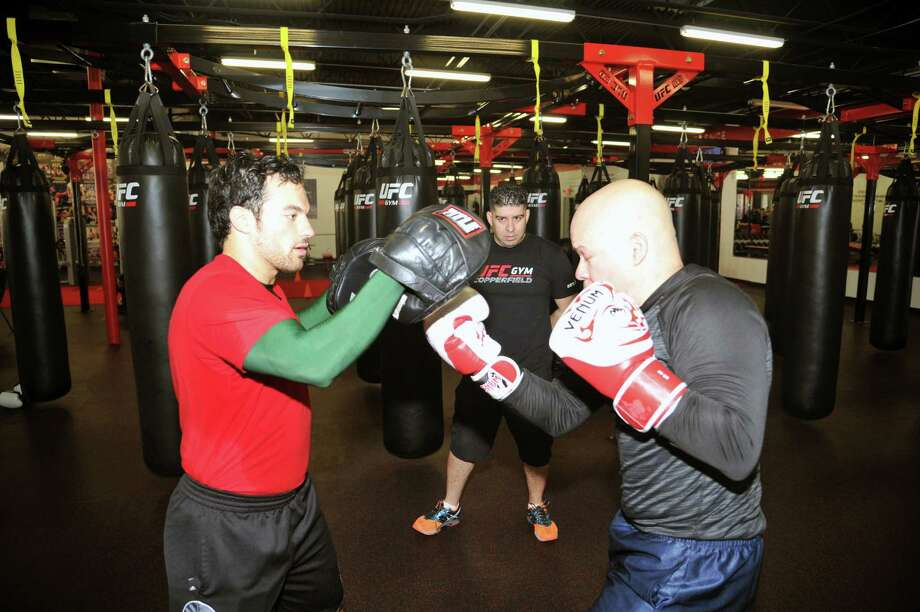 The UFC Gym in West Houston, operated by Steve and Ana Marie Hernandez, is celebrating its first-year anniversary. Left, Dionel Alves spars with Carlos Montanez, right, as gym owner Steve Hernandez, center, looks on. Photo: Eddy Matchette, Freelance / Freelance