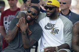 Cleveland Cavaliers' LeBron James, right, and Kyrie Irving hug during a rally Wednesday, June 22, 2016, in Cleveland. The Cavaliers made history by overcoming a 3-1 deficit to beat the Golden State Warriors in the NBA Finals and end the city's 52-year drought without a professional sports championship. (AP Photo/Tony Dejak)