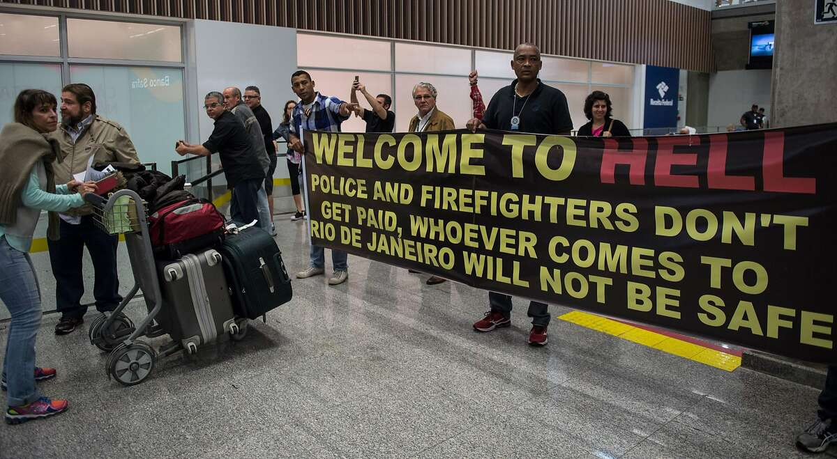 Police officers have been welcoming travelers to the international airport in Rio with banners reading