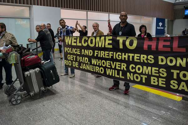 "Police officers welcome passengers with a banner reading ""Welcome to Hell"" and other slogans as they protest against the government for delay in their salary payments at Tom Jobim International Airport in Rio de Janeiro, Brazil, July 4, 2016. The Police has been mounting street protests since last week, saying that they have not been fully paid for months as Rio state's budget hovers on the edge of bankruptcy. Earlier this month, the state authorities in Rio declared ""state of public calamity ""about a major crisis budget in order to release emergency funds to finance the Olympic Games due to start in August. / AFP PHOTO / VANDERLEI ALMEIDAVANDERLEI ALMEIDA/AFP/Getty Images"