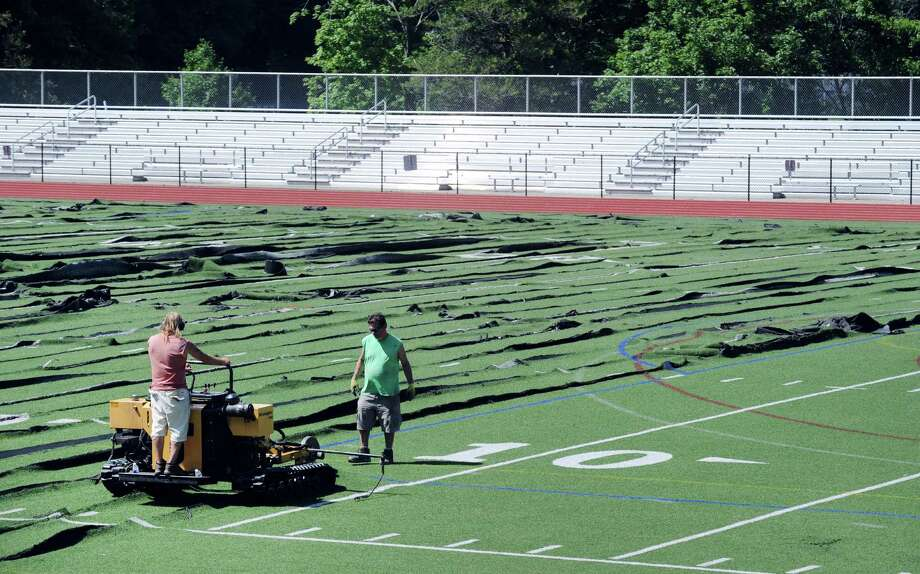 A crew of workers from APW Enterprises of Sherman, Conn., pulls up the artificial turf at Greenwich High School's Cardinal Stadium, Greenwich, Conn., Tuesday, July 5, 2016. Allen Waterman of APW Enterprises who was supervising the removal said that it would take about three-four days to complete the job. Waterman said the field has an intricate drainage system and the track is also connected to the turf so it is a lot more than just ripping up turf, that great care is required so that the job is done properly. Waterman also said the new field will be installed in the near future by the SPRINTURF Company. Photo: Bob Luckey Jr. / Hearst Connecticut Media / Greenwich Time