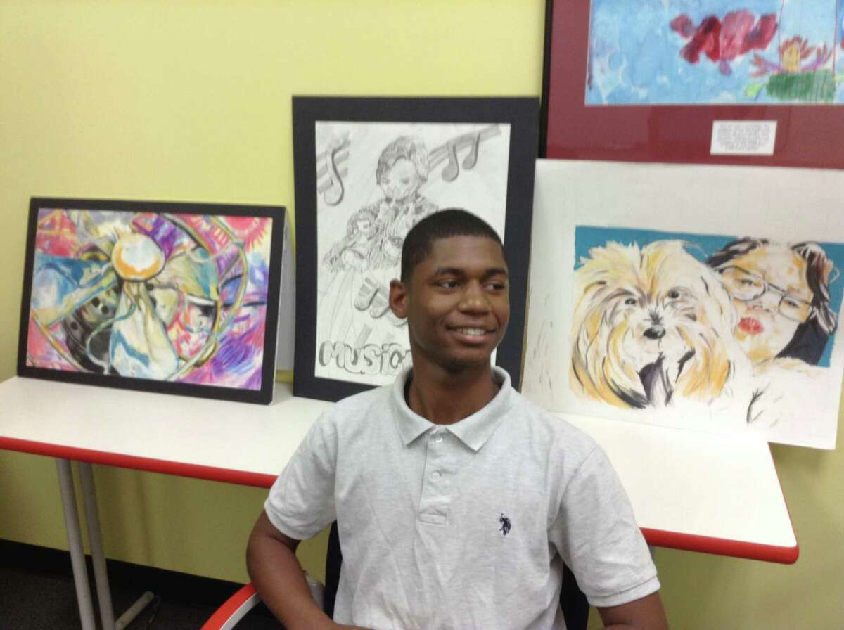 Juqua Gamble in front of his artwork at Child Protective Services office, June 30, 2016 in Houston