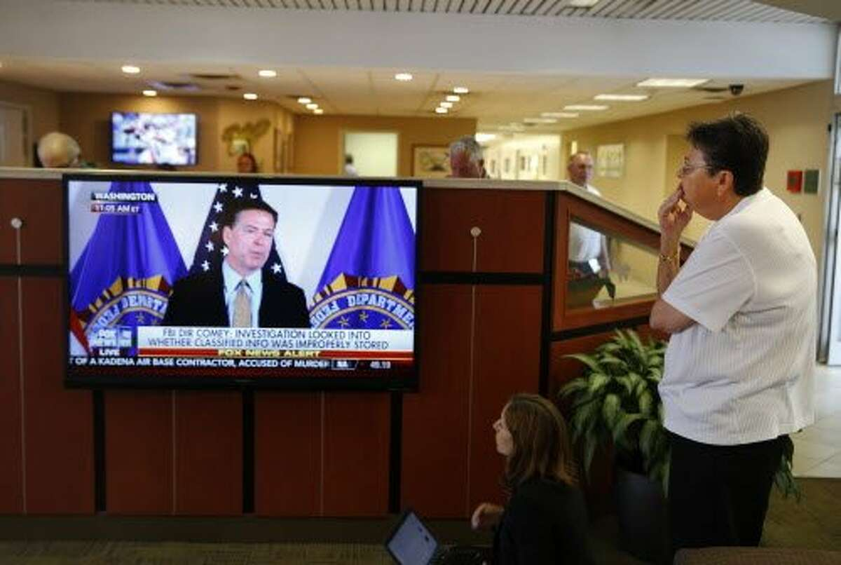 A woman watches as FBI Director James Comey announces the results of his department's investigation into former Secretary of State and Democratic presidential candidate Hillary Clinton's handling of classified emails, Tuesday, July 5, 2016, in Charlotte, N.C.. Clinton is expected to appear with at President Barack Obama in Charlotte later Tuesday. (AP Photo/John Bazemore)