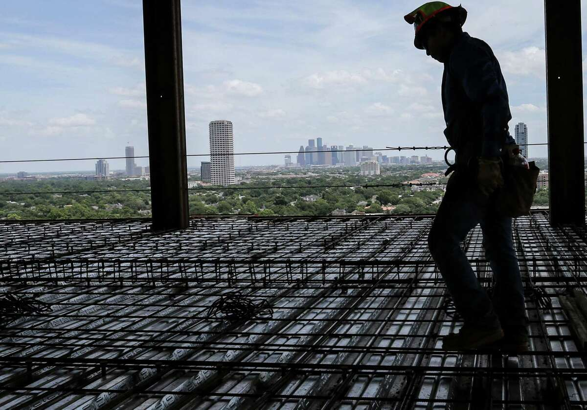 Construction workers work on the penthouses at 3433 Westheimer Road, photographed on Tuesday, July 5, 2016, in Houston. ( Elizabeth Conley / Houston Chronicle )