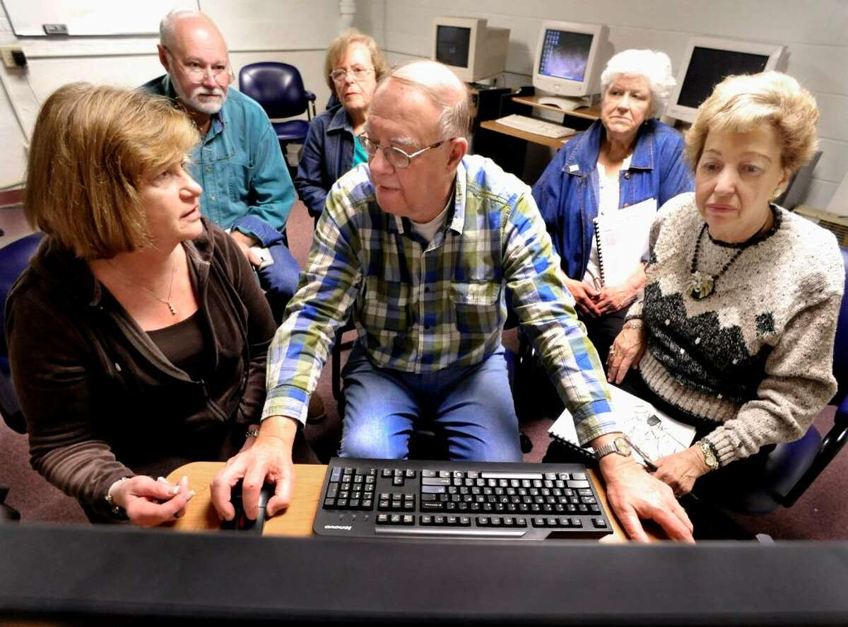 Madelaine Gross questions volunteer instructor Bob Baron during a computer class at the Bethel Senior Center on Friday, April 17, 2010. At right is Connie Meehan. In the back row from left are, Japeth Turley,Pat Zona and Marguerite Linse.