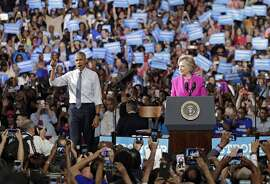 President Barack Obama, left, gestures as Democratic presidential candidate Hillary Clinton, right, takes the podium during a campaign rally for Clinton in Charlotte, N.C., Tuesday, July 5, 2016. (AP Photo/Chuck Burton)