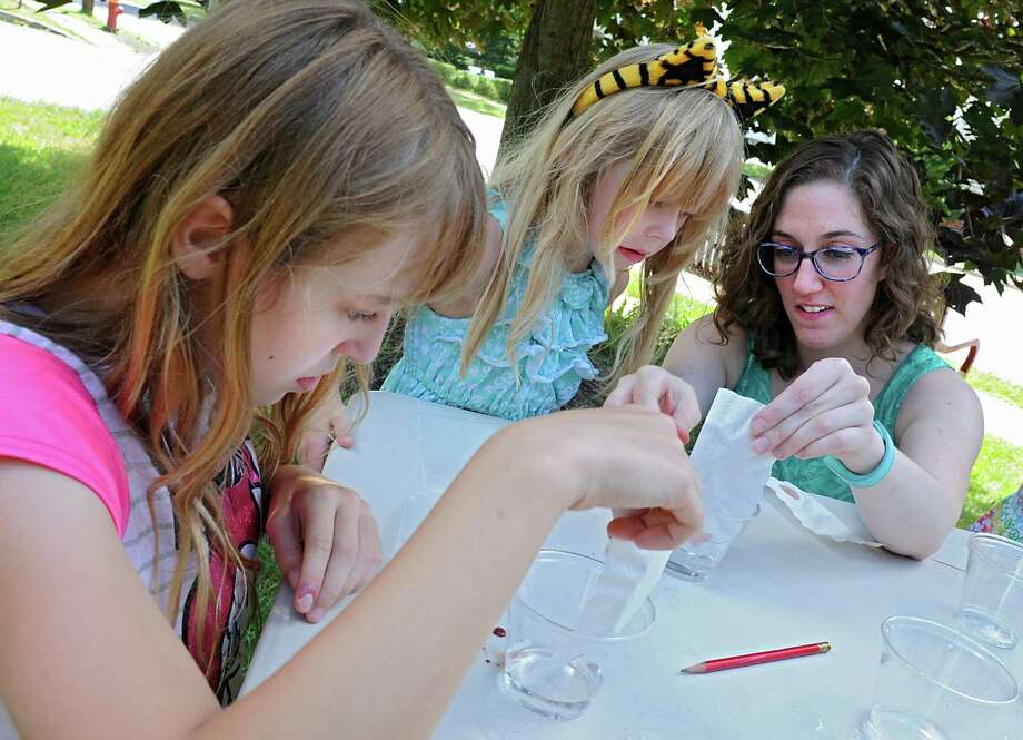Mia Orobona, youth services librarian, right, teaches the process of candy chromatography to Isabelle Ridgeway, 12, left, of Castleton-On-Hudson and her sister Jaclyn, 6, during a sidewalk science class in front of the library on Tuesday, July 5, 2016 in the Village of Castleton, N.Y. (Lori Van Buren / Times Union) Photo: Lori Van Buren / 20037227A