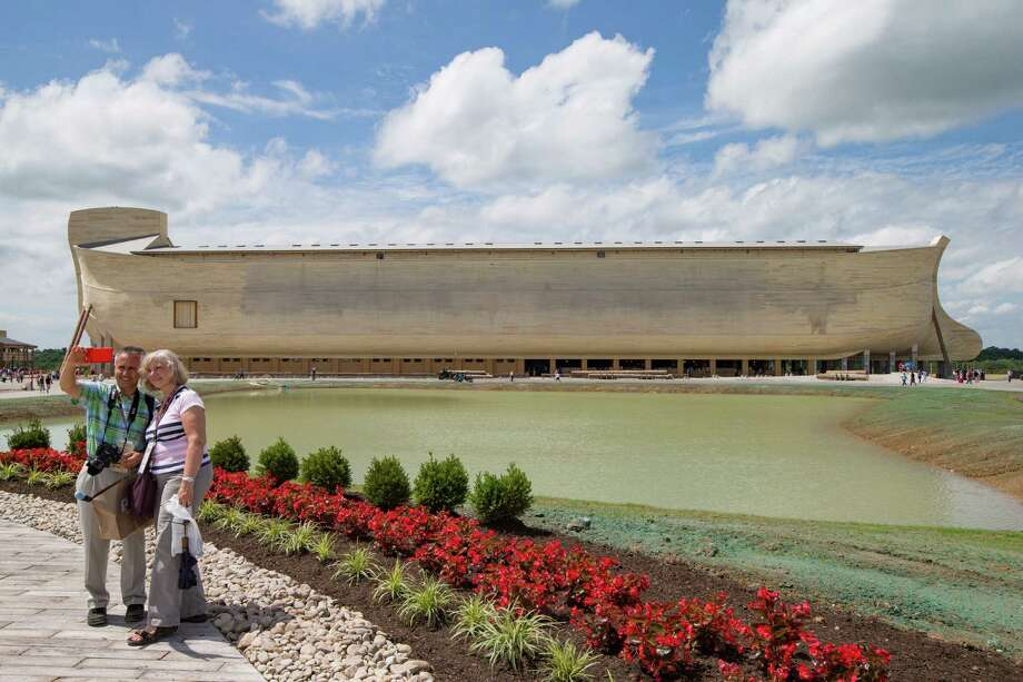 Visitors take a selfie as a replica Noah's Ark stands in the distance at the Ark Encounter theme park during a media preview day, Tuesday, July 5, 2016, in Williamstown, Ky. The long-awaited theme park based on the story of a man who got a warning from God about a worldwide flood will debut in central Kentucky this Thursday. The Christian group behind the 510 foot-long wooden ark says it will demonstrate that the stories of the Bible are true. Its construction has rankled opponents who say the attraction will be detrimental to science education. (AP Photo/John Minchillo) ORG XMIT: KYJM127 Photo: John Minchillo / AP
