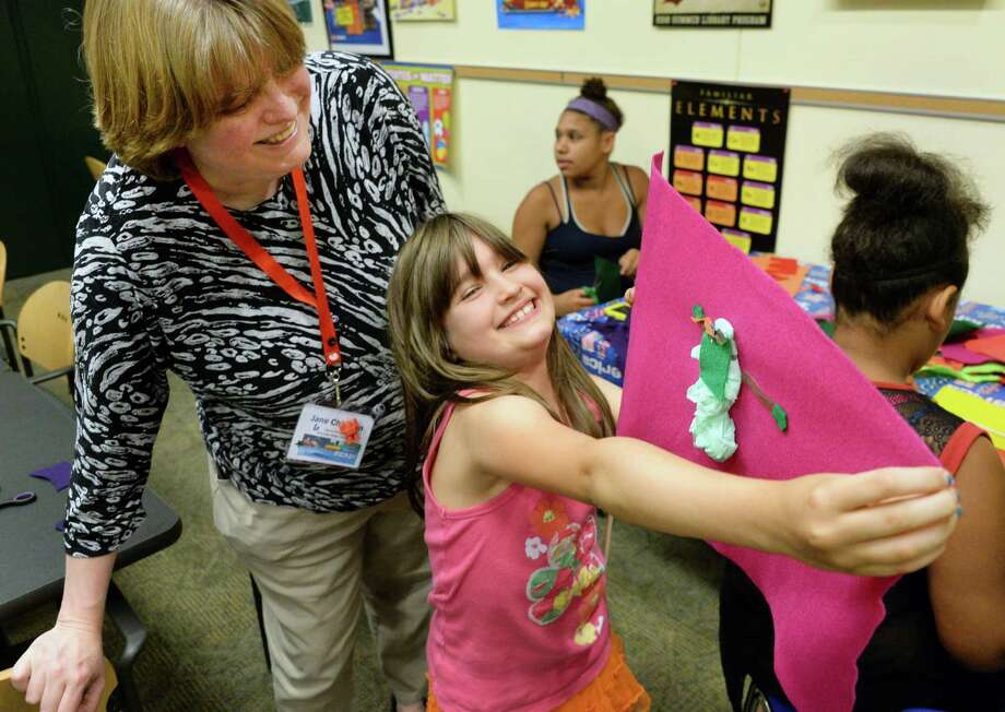Library director Jane Chirgwin takes a look at the flag designed and made by Angelica Lawrence, 7, of Rensselaer during a Maker Lab at the Rensselaer Public Library Tuesday July 5, 2016 in Rensselaer, NY.  (John Carl D'Annibale / Times Union) Photo: John Carl D'Annibale / 20037226A