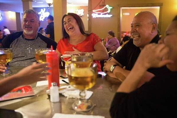 From left, Humberto Chavana, Monica Ramos, Roland Gonzales and Deborah Amaya share a laugh over beers at M.K. Davis.