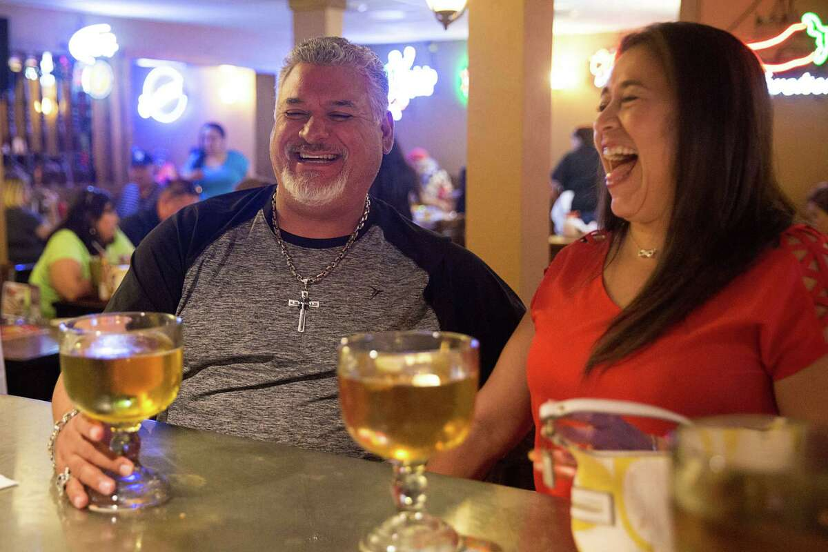 Humberto Chavana, left, and Monica Ramos share a laugh over beers at M.K. Davis.