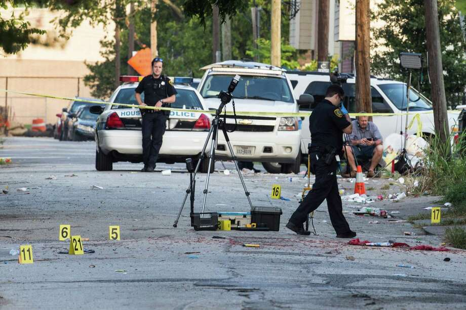 Police investigate the scene of a fatal shooting in the 1300 block of Robin on Tuesday, July 5, 2016. Three people were killed during a 4th of July party near downtown.  Photo: Brett Coomer, Staff / © 2016 Houston Chronicle