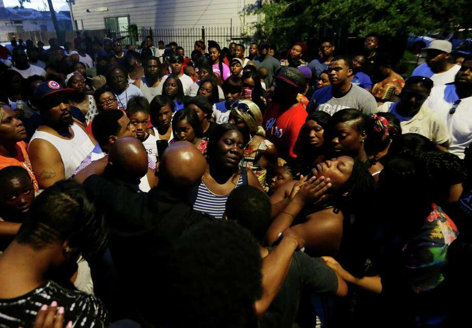 Community members pray around the family of Charles Jackson during a vigil Tuesday at the site of Monday's deadly shooting.  Photo: Mark Mulligan / © 2016 Houston Chronicle
