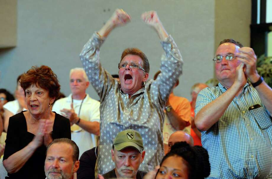 Black Rock resident Peggy Faucher, center, protests with hundreds of others over a raise in property taxes during the Bridgeport City Council's meeting at City Hall on Tuesday. Photo: Christian Abraham / Hearst Connecticut Media / Connecticut Post