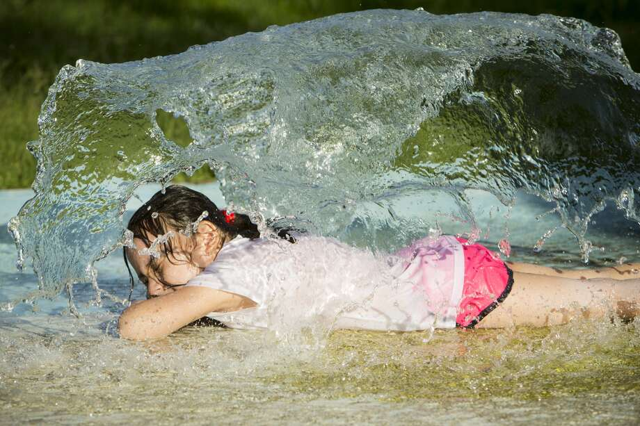 Mia Cervantes, 5, beats the heat as she plays in the fountains at Monite Beach Park on Wednesday, July 6, 2016, in Houston. Temperatures are forecast into the high 90s. ( Brett Coomer / Houston Chronicle )