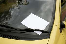 A note left under windscreen wipers of a car add own text.