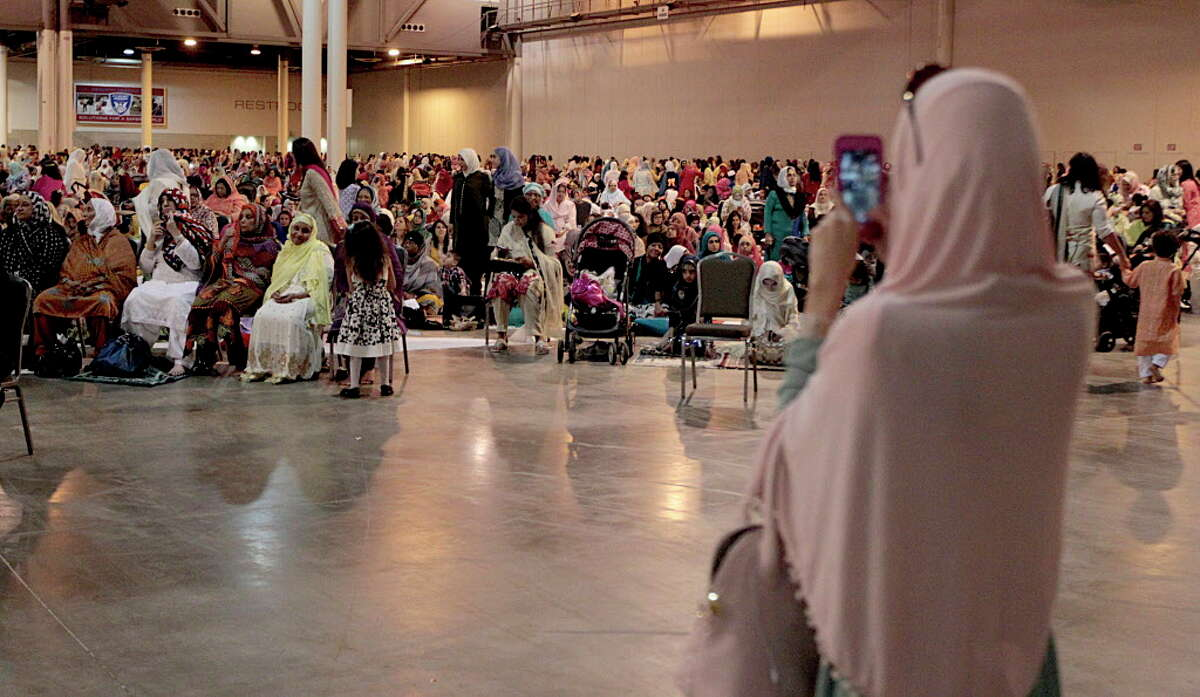 A woman takes a cellphone video during The Islamic Society of Greater Houston Eid celebration at NRG Center July 6, 2016, in Houston.