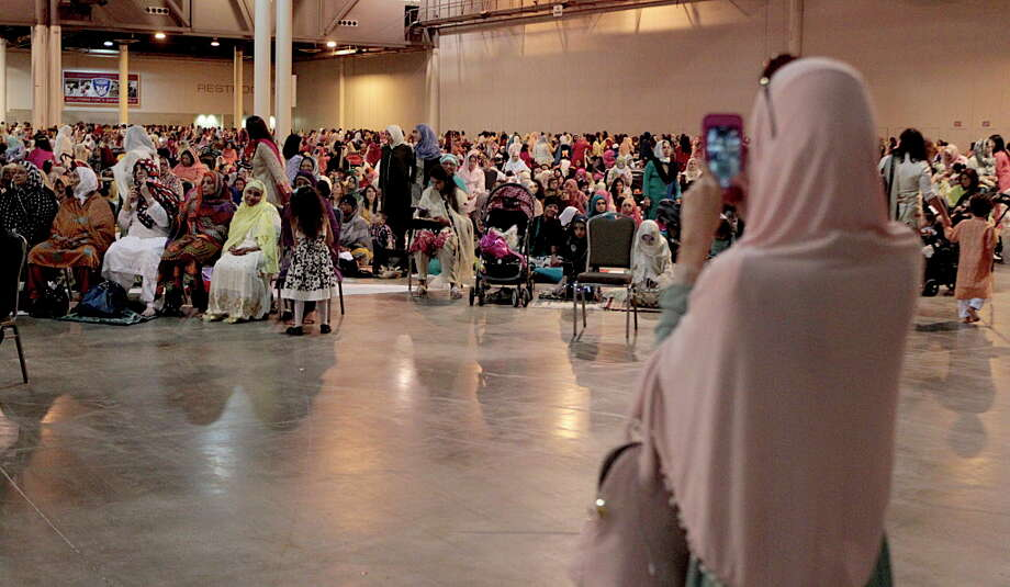 A woman takes a cellphone video during The Islamic Society of Greater Houston Eid celebration at NRG Center July 6, 2016, in Houston. Photo: James Nielsen, Houston Chronicle / © 2016  Houston Chronicle