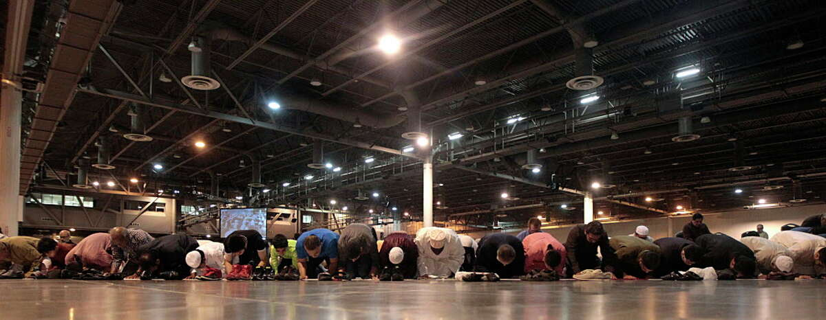 Men kneel in prayer during The Islamic Society of Greater Houston Eid celebration at NRG Center July 6, 2016, in Houston.