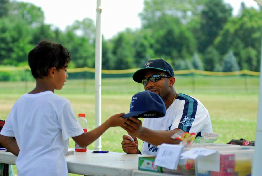 Former Major League Baseball player and current Bridgeport Bluefish outfielder Endy Chavez signs autographs for youngsters during a Baseball World clinic held on Wednesday, July 6th, 2016 at Bedford Middle School in Westport, Connecticut. Photo: Ryan Lacey/Hearst Connecticut Media / Westport News Contributed