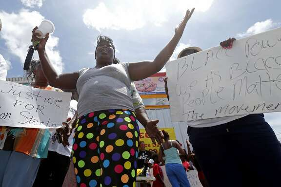 Regina Adams, who said she knew Alton Sterling since he was a baby, speaks out as people gather outside the Triple S convenience store in Baton Rouge, La., Wednesday, July 6, 2016. Sterling, 37, was shot and killed by Baton Rouge police Tuesday outside the store where he was selling CDs. The U.S. Justice Department opened a civil rights investigation Wednesday into the videotaped police killing of Sterling. (AP Photo/Gerald Herbert)
