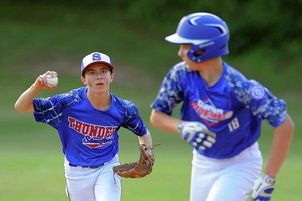 Darien's Chris Mancini, right, gets caught in a rundown with Stamford's James Miller in the third inning of Thursday's District 1 Babe Ruth Baseball 14s Championship game at Holahan Field in Darien.