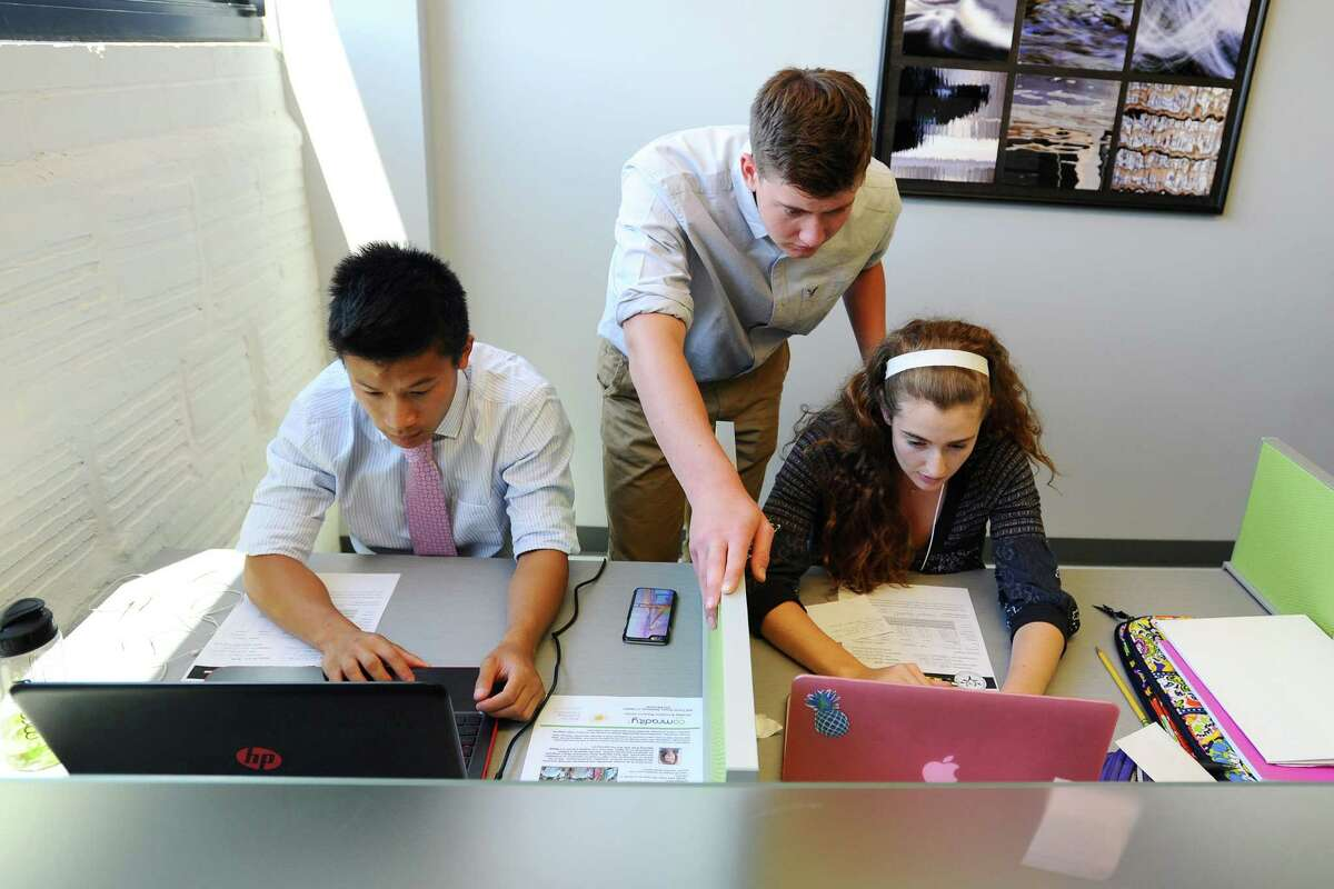 Jake Dardis, left, looks over Abby Bushell's shoulder while working together at Comradity on Thursday, June 30, 2016. Five rising seniors from Westhill High School and Stamford High School, including Dardis and Bushell, were placed at Comradity as part of the Mayor's Youth Employment Program. Also pictured is Charlie Teeters, left.