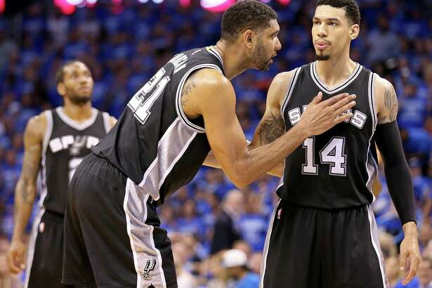 Spurs' Tim Duncan talks with Danny Green as Green shoots a free throw during second half action of Game 6 in the Western Conference semifinals against the Oklahoma City Thunder on May 12, 2016 at Chesapeake Energy Arena.