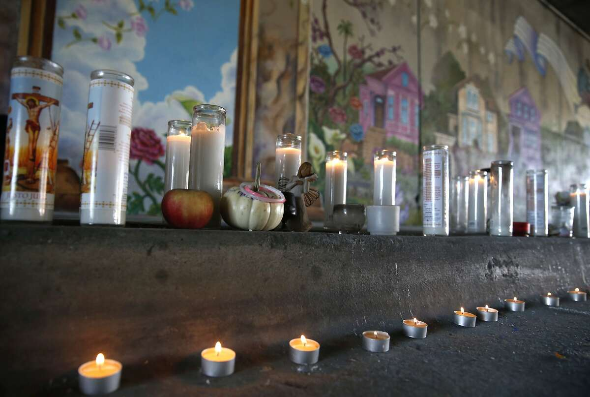 Candles line the curb at a dedication ceremony for the Superheroes Mural Project on West Street in Oakland, Calif. on Wednesday, Oct. 21, 2015. Artist Antonio Ramos was shot and killed while working on the mural on Sept. 29.