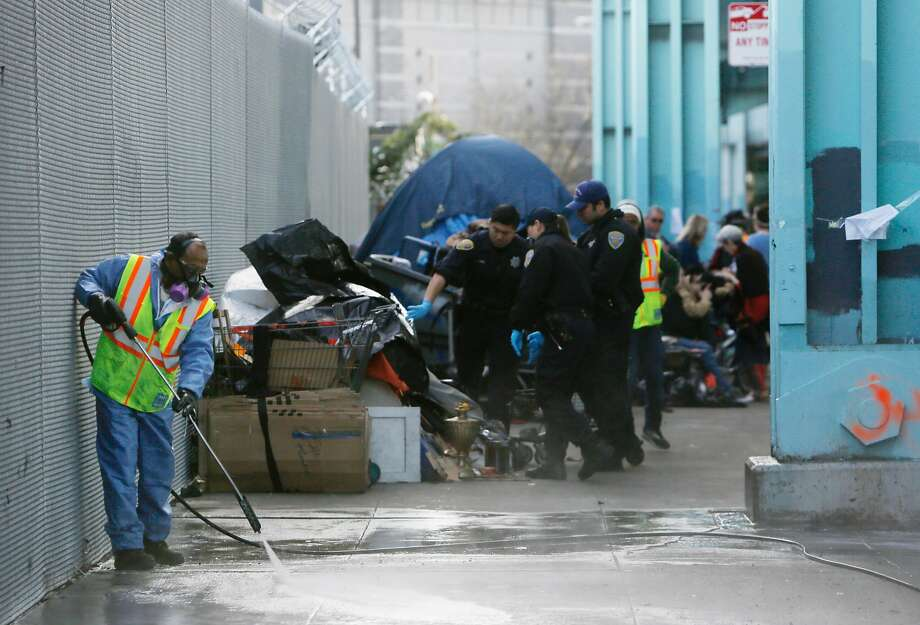 A Department of Public Works member cleans Division Street as city crews clear out a homeless encampment in March. Photo: Lea Suzuki, The Chronicle