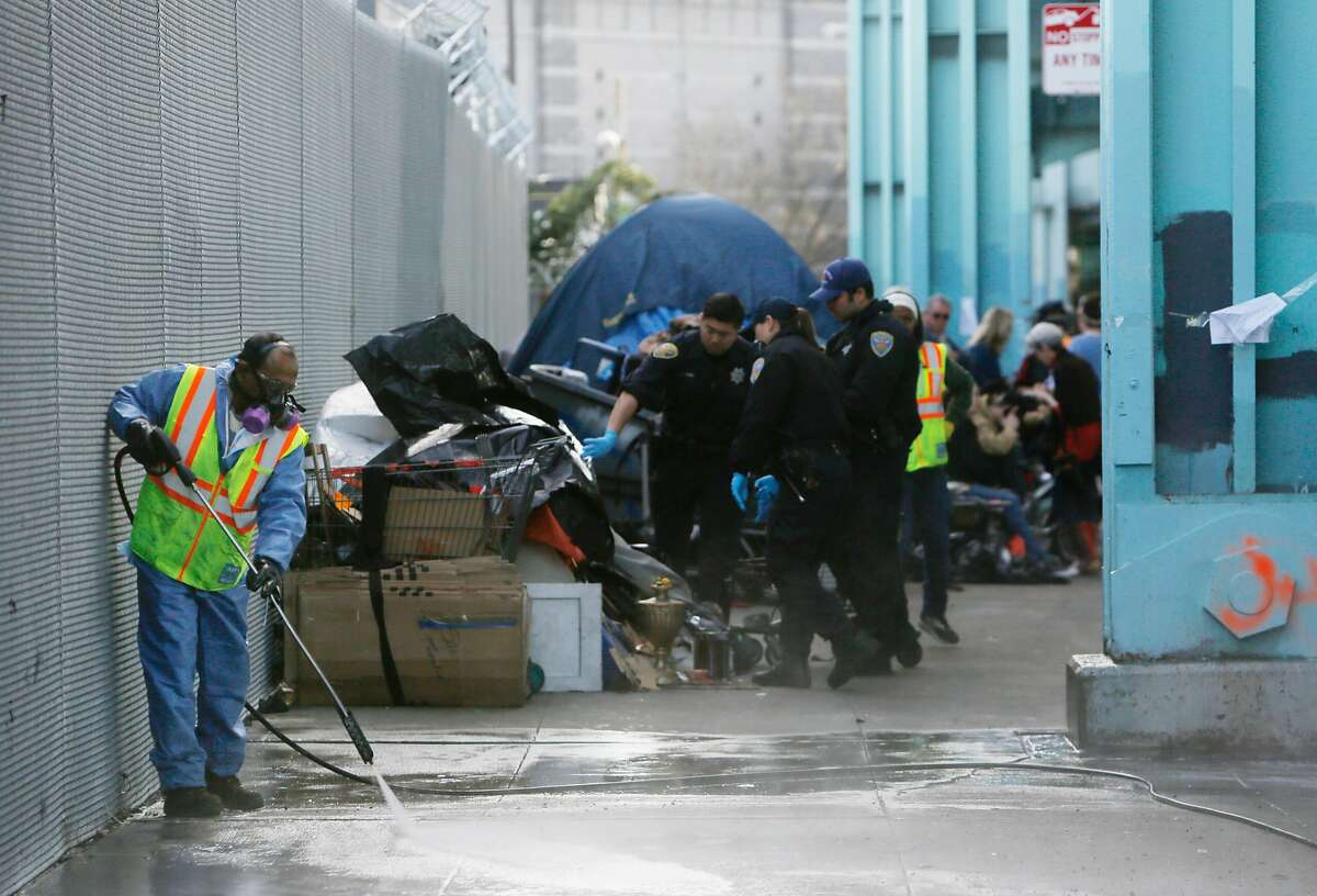 A Department of Public Works member cleans 13th Street as city work crews clear out a homeless encampment along 13th Street in the morning on Tuesday, March 1, 2016 in San Francisco, California.