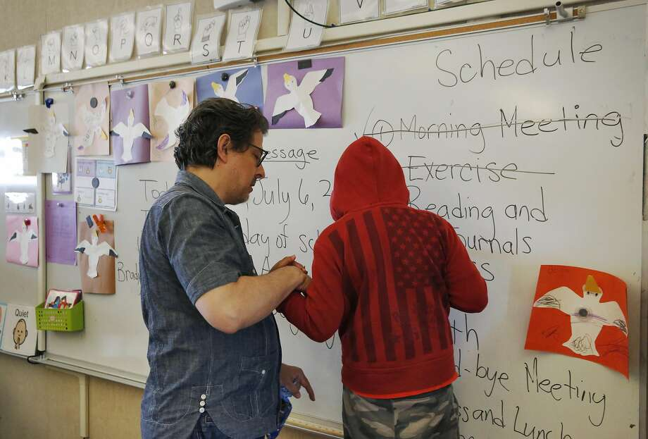 Special education teacher George Keller helps a student balance as he writes on a whiteboard  at Sunset Elementary School in San Francisco. Special education teachers are among the most in demand. Photo: Leah Millis, The Chronicle