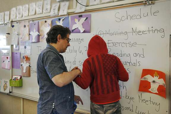 Special Education teacher George Keller helps a student balance as he writes on the white board during the last class of the extended school year for special education students at Sunset Elementary School July 6, 2016 in San Francisco, Calif.