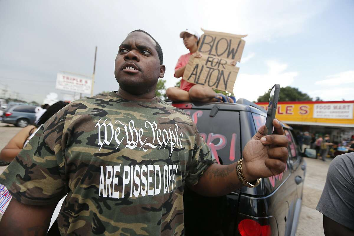 Charley Roggerson films with his cellphone people outside the Triple S convenience store during a rally after Alton Sterling, a black man, was shot and killed Tuesday, in Baton Rouge, La., Wednesday, July 6, 2016. The U.S. Justice Department opened a civil rights investigation Wednesday into the video-recorded police killing of Sterling, who authorities say had a gun as he wrestled with two white officers on the pavement outside a convenience store. (AP Photo/Gerald Herbert)